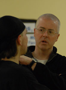 Fr. Obrien talks with teen at basketball practice